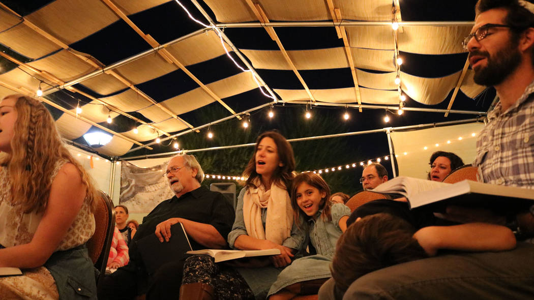 Cassidy Wertheimer, center, and her daughter Magnolia, 6, join in Sabbath prayer under the Sukkah at Congregation Ner Tamid in Henderson, Friday, Oct. 6, 2017. Janna Karel Las Vegas Review-Journal