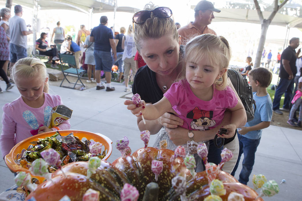 Rachel Kirkendall lifts up daughter Elise, 2, to grab a pice of candy at Heritage Harvest Festival  in Henderson, Saturday, Oct. 7, 2017.  Bridget Bennett Las Vegas Review-Journal @Bridgetkbennett