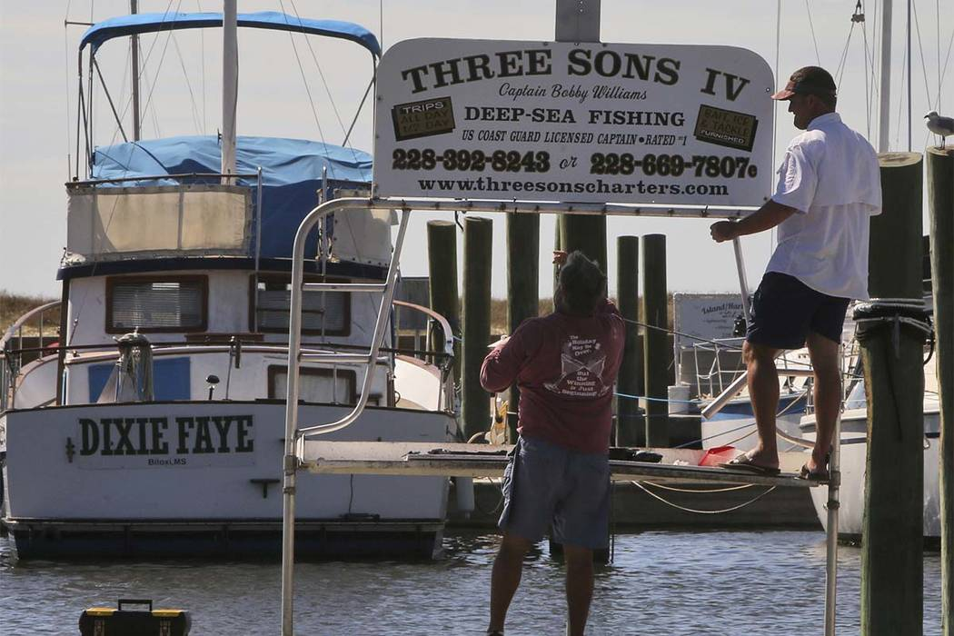 Bobby Williams, left, and his son, Bobby, Jr., take down the sign for their charter boat at the Biloxi, Mississippi, Small Craft Harbor on Friday, Oct. 6, 2017.  Gulf Coast residents were bracing  ...