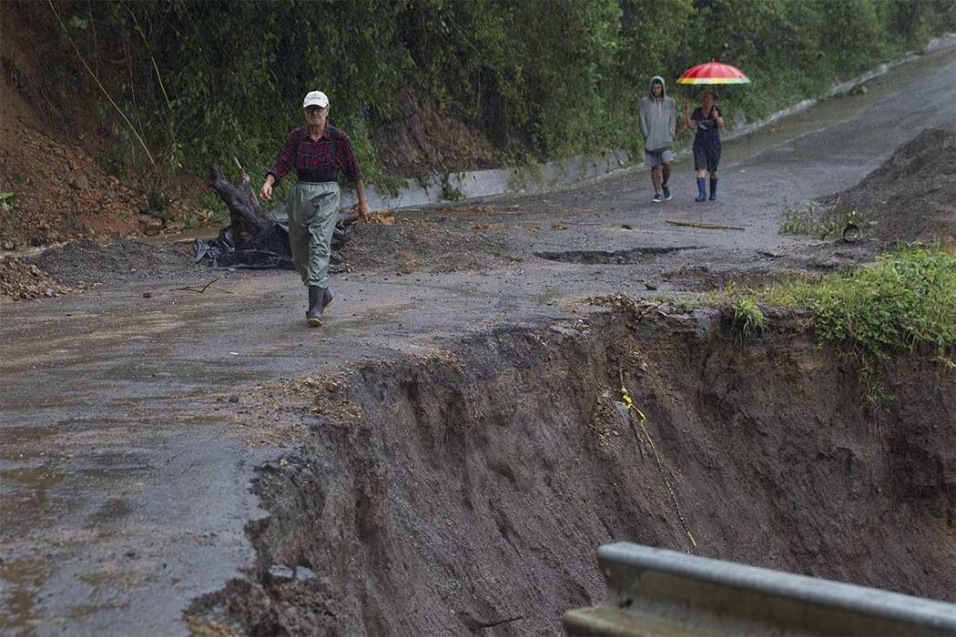 Neighbors walk under the rain past a washed out road in Alajuelita on the outskirts of San Jose, Costa Rica, Thursday, Oct. 5, 2017. Tropical Storm Nate formed off the coast of Nicaragua on Thursd ...