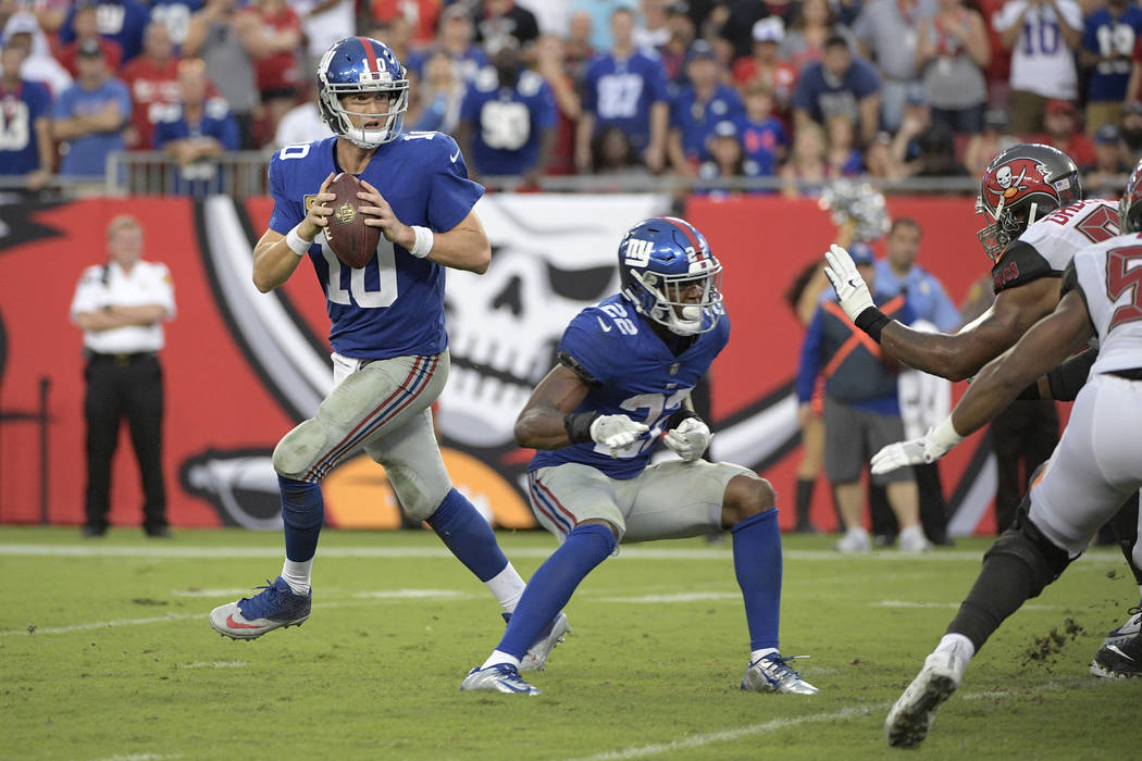 New York Giants quarterback Eli Manning (10) looks for an open receiver as running back Wayne Gallman (22) sets up to block during the second half of an NFL football game against the Tampa Bay Buc ...