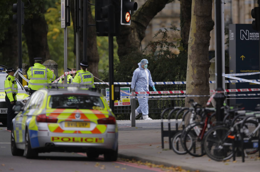 Britain's Police and a forensic investigator at the scene of an incident in central London, Saturday, Oct. 7, 2017. London police say emergency services are outside the Natural History Museum in L ...
