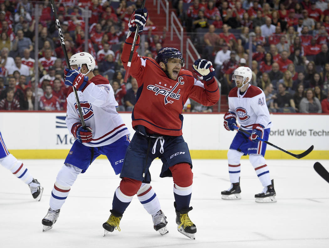 Washington Capitals left wing Alex Ovechkin (8), of Russia, celebrates his goal next to Montreal Canadiens defenseman Karl Alzner (22) during the first period of a NHL hockey game, Saturday, Oct.  ...