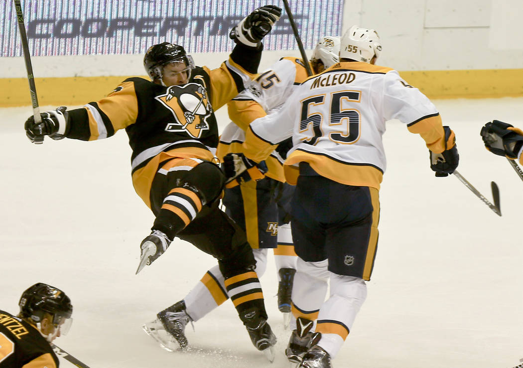 Pittsburgh Penguins' Sidney Crosby (87) is checked by Craig Smith (15) in the first period of the NHL hockey game, Saturday, Oct. 7, 2017, in Pittsburgh. (AP Photo/Keith Srakocic)