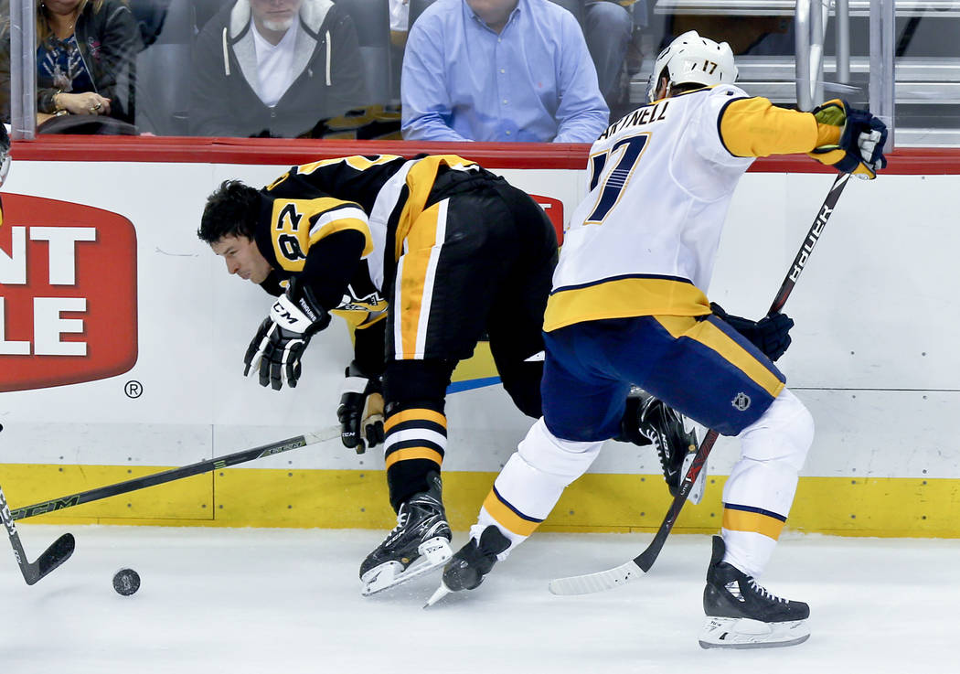 Pittsburgh Penguins' Sidney Crosby (87) hits the boards after losing his helmet after getting hit by Nashville Predators' Scott Hartnell (17) in the third period of the NHL hockey game, Saturday,  ...