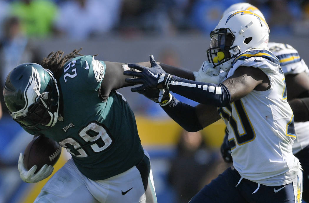 Philadelphia Eagles running back LeGarrette Blount, left, gets a hand on the face mask of Los Angeles Chargers defensive back Desmond King (20) as he runs during the second half of an NFL football ...