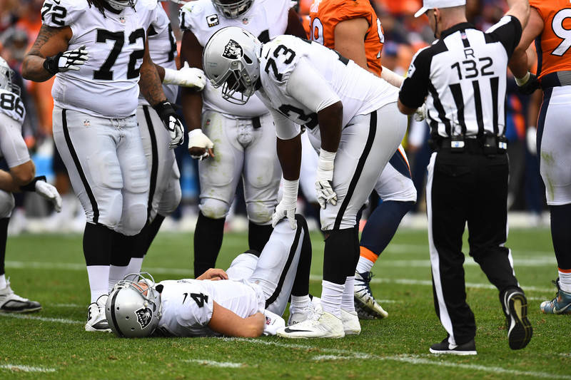 Oct 1, 2017; Denver, CO, USA; Oakland Raiders offensive tackle Marshall Newhouse (73) looks at  injured Oakland Raiders quarterback Derek Carr (4) in the second half against the Denver Broncos at  ...