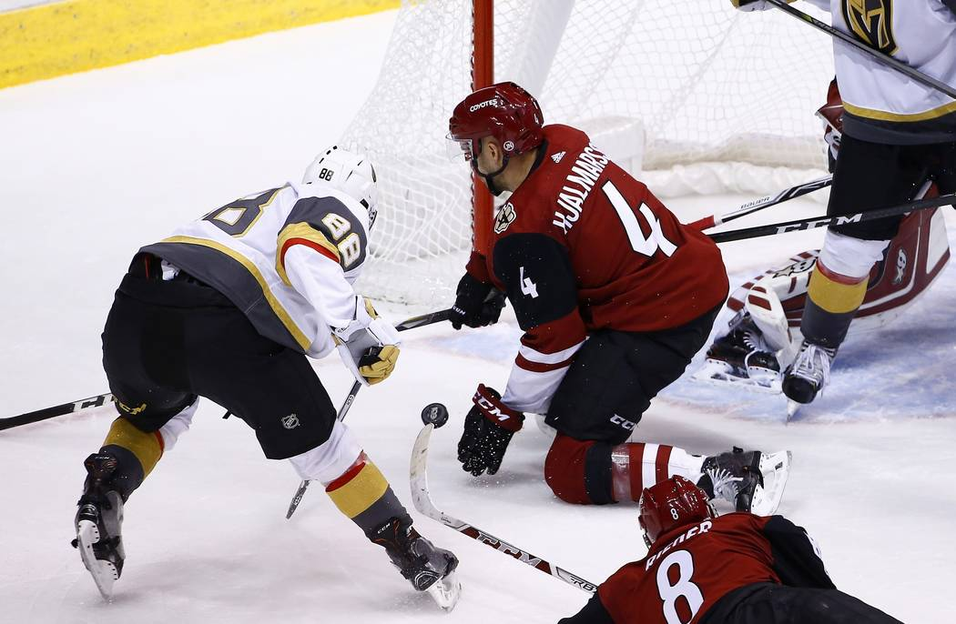 Vegas Golden Knights defenseman Nate Schmidt (88) sends the puck past Arizona Coyotes defenseman Niklas Hjalmarsson (4) for a goal during the third period of an NHL hockey game Saturday, Oct. 7, 2 ...