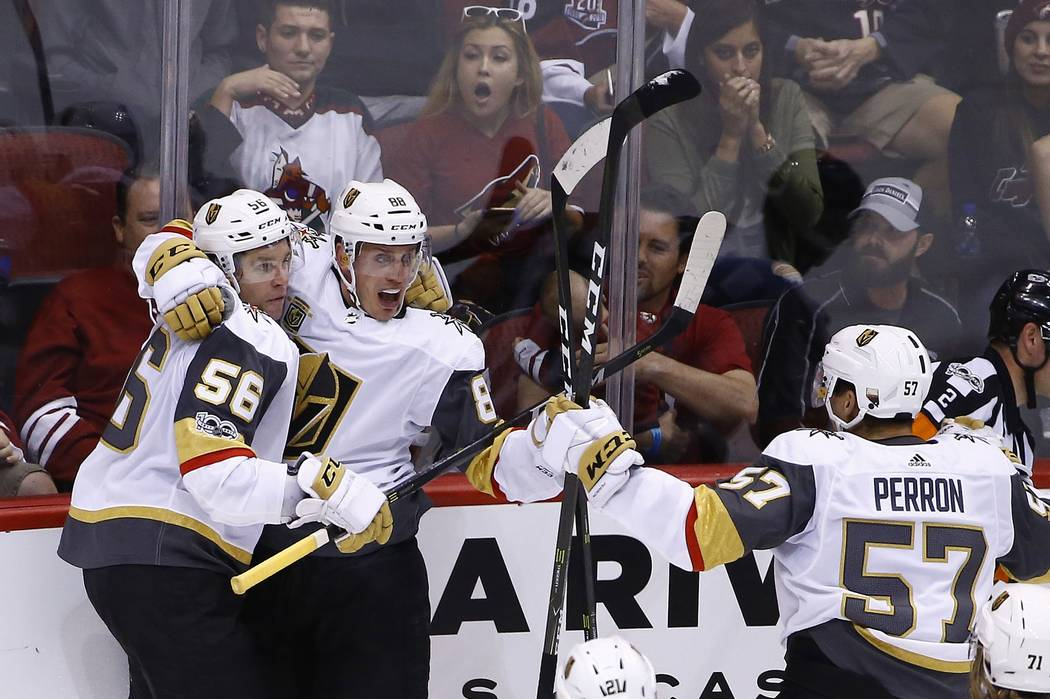 Vegas Golden Knights defenseman Nate Schmidt (88) celebrates his goal scored against the Arizona Coyotes with Golden Knights left wing Erik Haula (56) and Golden Knights left wing David Perron (57 ...