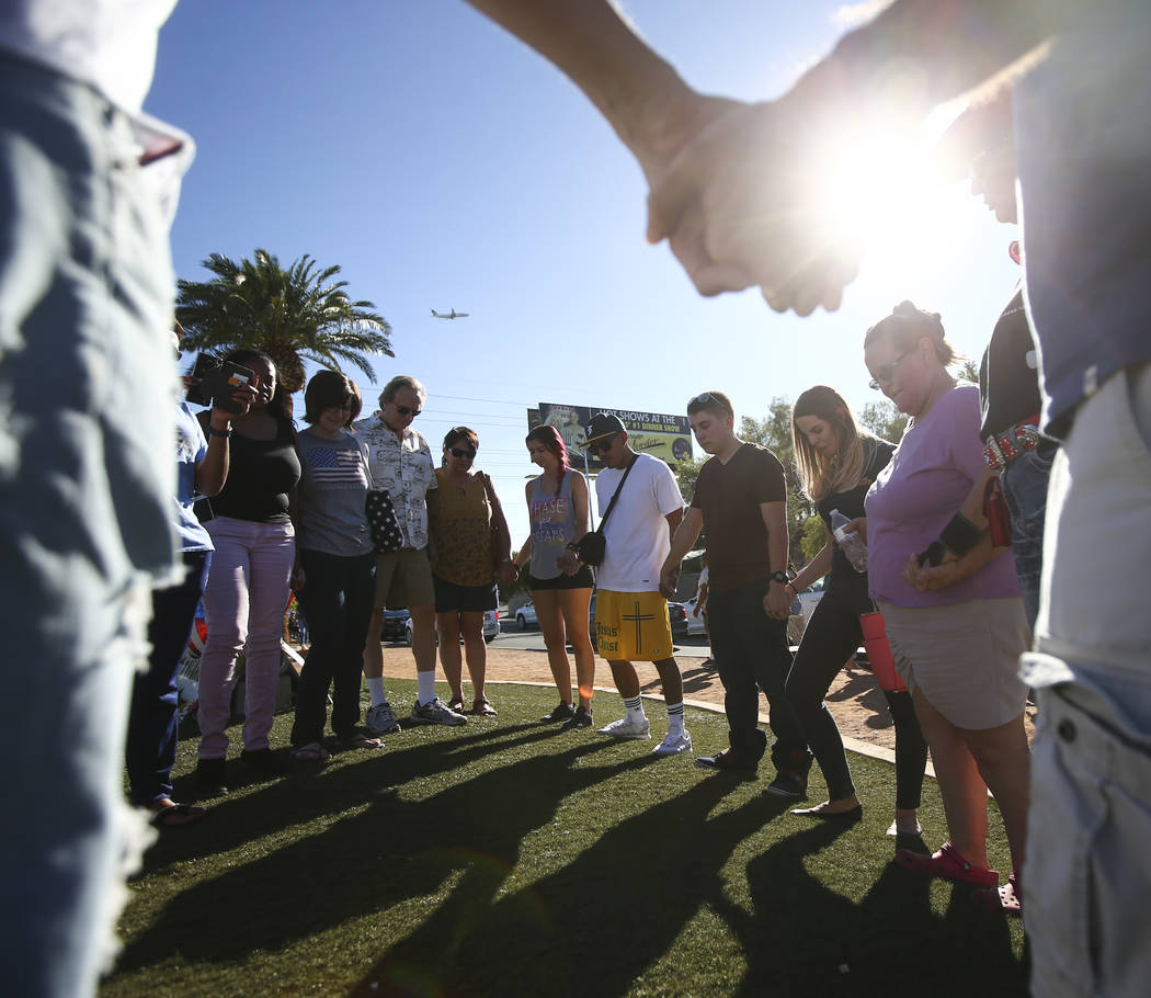 "People pray near a makeshift memorial for victims of Sunday's mass shooting near the ""Welcome to Fabulous Las Vegas"" sign in Las Vegas on Saturday, Oct. 7, 2017. Chase Stevens La ..."