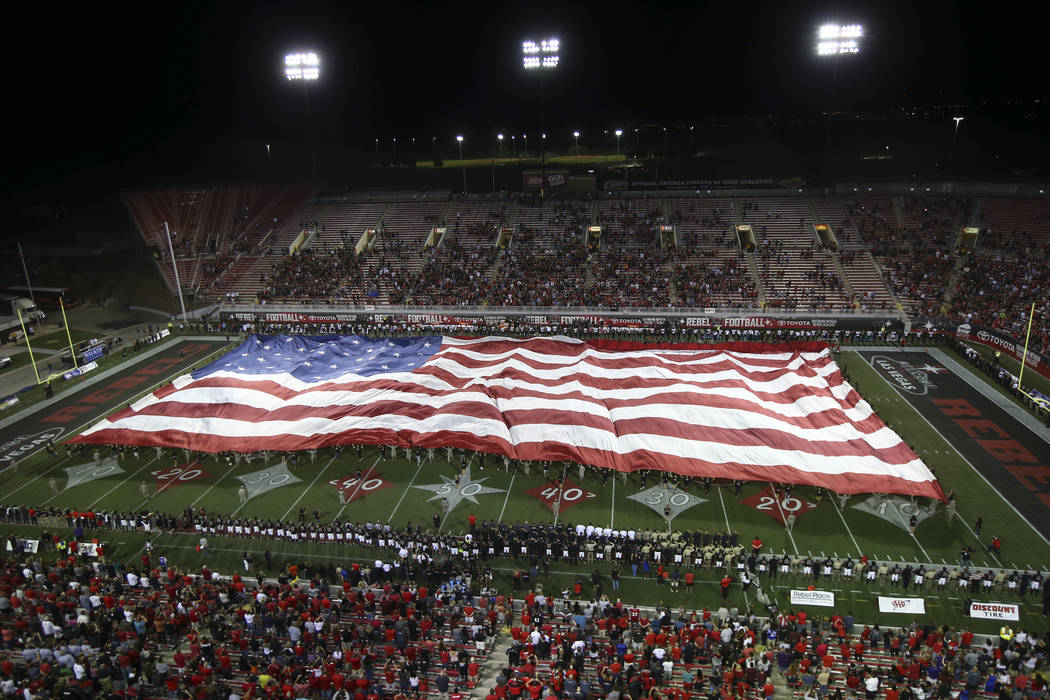 The American flag, honoring the victims of Sunday's mass shooting, is unfurled before a football game between UNLV and San Diego State at Sam Boyd Stadium in Las Vegas on Saturday, Oct. 7, 2017. C ...