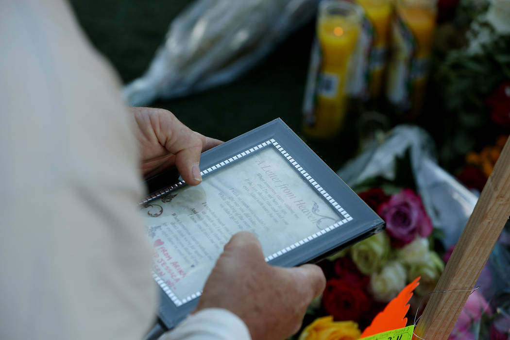 A man holds a poem while grieving at a memorial across the street from the Mandalay Bay and the Route 91 Harvest Festival grounds in Las Vegas, Saturday, Oct. 7, 2017. Elizabeth Brumley Las Vegas  ...