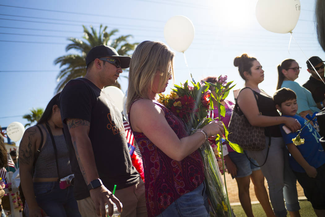 "Las Vegas resident Heather Harrison, with her fiancee Jason Hernandez, left, brought flowers to leave at a makeshift memorial for victims of Sunday's mass shooting near the ""Welcome to Fa ..."