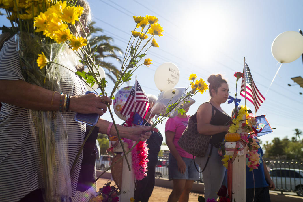 "Sharon Miller of Las Vegas leaves flowers at a makeshift memorial for victims of Sunday's mass shooting near the ""Welcome to Fabulous Las Vegas"" sign in Las Vegas on Saturday, Oc ..."
