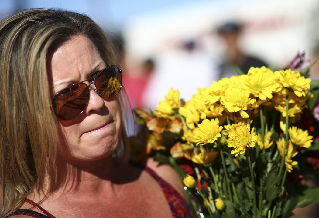 "Las Vegas resident Heather Harrison brought flowers to a makeshift memorial for victims of Sunday's mass shooting near the ""Welcome to Fabulous Las Vegas"" sign in Las Vegas on Sa ..."