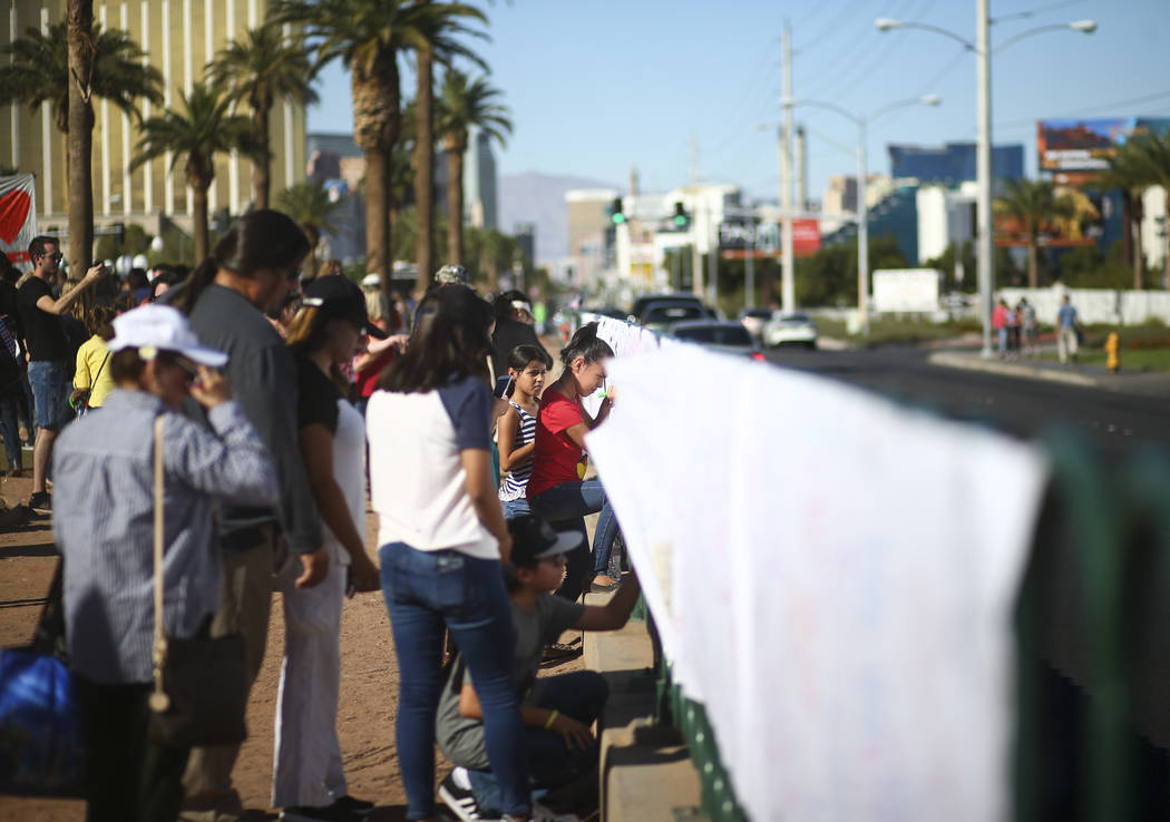 "People leave messages on a sign near a makeshift memorial for victims of Sunday's mass shooting near the ""Welcome to Fabulous Las Vegas"" sign in Las Vegas on Saturday, Oct. 7, 20 ..."