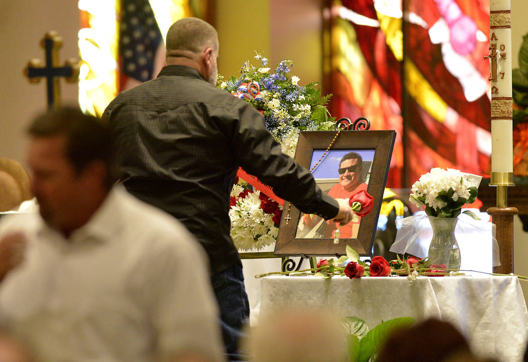 A pallbearer lays a rose next to a photo of Jack Beaton during his memorial service at St. Elizabeth Ann Seton Catholic Church in Bakersfield, Calif., on Saturday, Oct. 7, 2017. Beaton was a victi ...