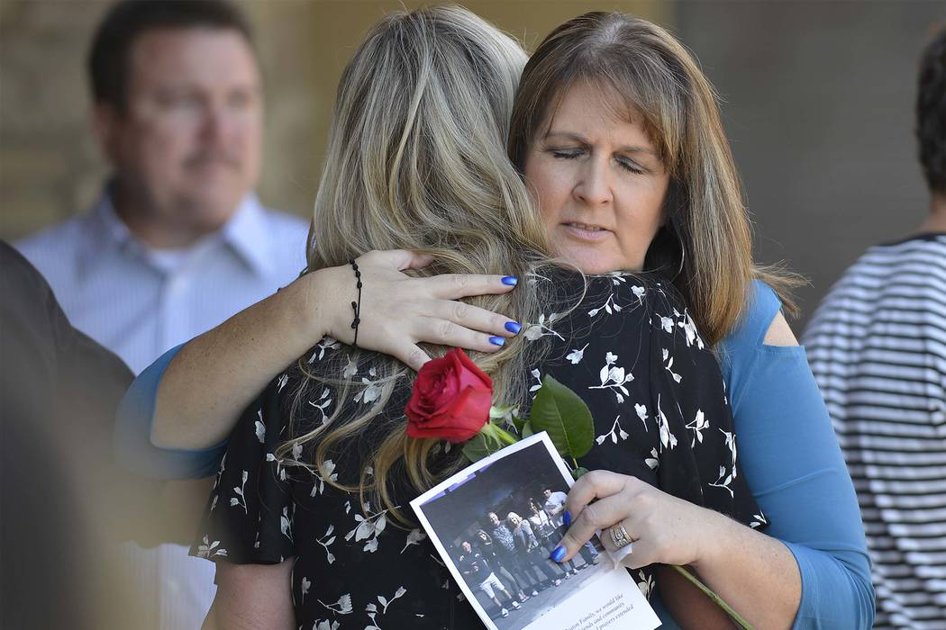 Laurie Beaton, right, hugs a mourner after a memorial service for her husband, Jack Beaton at St. Elizabeth Ann Seton Catholic Church in Bakersfield, Calif., on Saturday, Oct. 7, 2017. Beaton was  ...