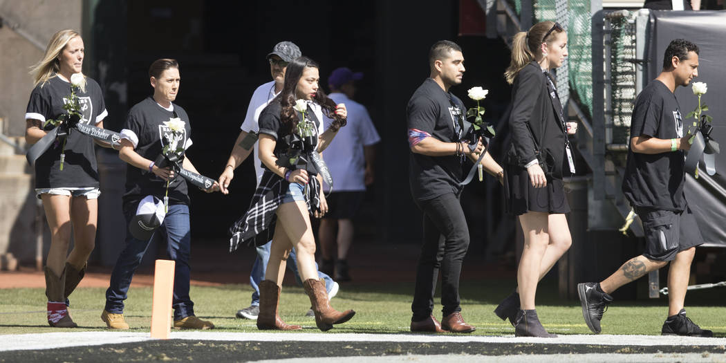 Members of Raider Nation come out before the game with roses and ribbons to pay tribute to the victims of the mass shooting in Las Vegas in Oakland, Calif., Sunday, Oct. 8, 2017. Heidi Fang Las Ve ...