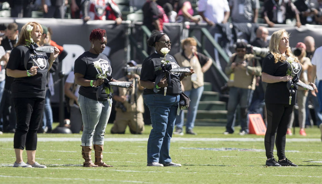 Members of Raider Nation come out before the game with roses and ribbons with names of the fallen on them to pay tribute to the victims of the mass shooting in Las Vegas in Oakland, Calif., Sunday ...