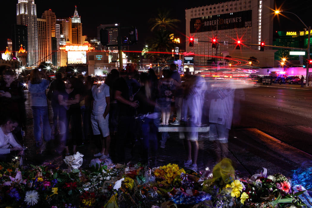 People gather as some lights along the Strip turned off at 10:05 p.m. for 11 minutes marking exactly one week after the mass shooting at the Route 91 Harvest Festival in Las Vegas, Sunday, Oct. 8, ...