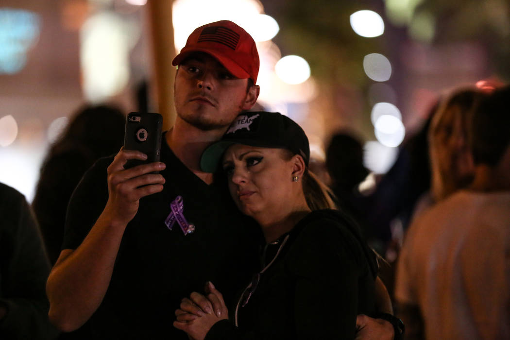Andrew Fusaro, 23, left, and Kristy-Marie Hoff, 32, right, both of Las Vegas, hug as some lights along the Strip turned off at 10:05 p.m. for 11 minutes marking exactly one week after the mass sho ...