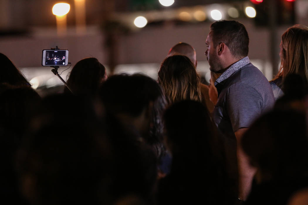 People gather as some lights turned off at 10:05 p.m. for 11 minutes marking exactly one week after the mass shooting at the Route 91 Harvest Festival in Las Vegas, Sunday, Oct. 8, 2017. Joel Ange ...