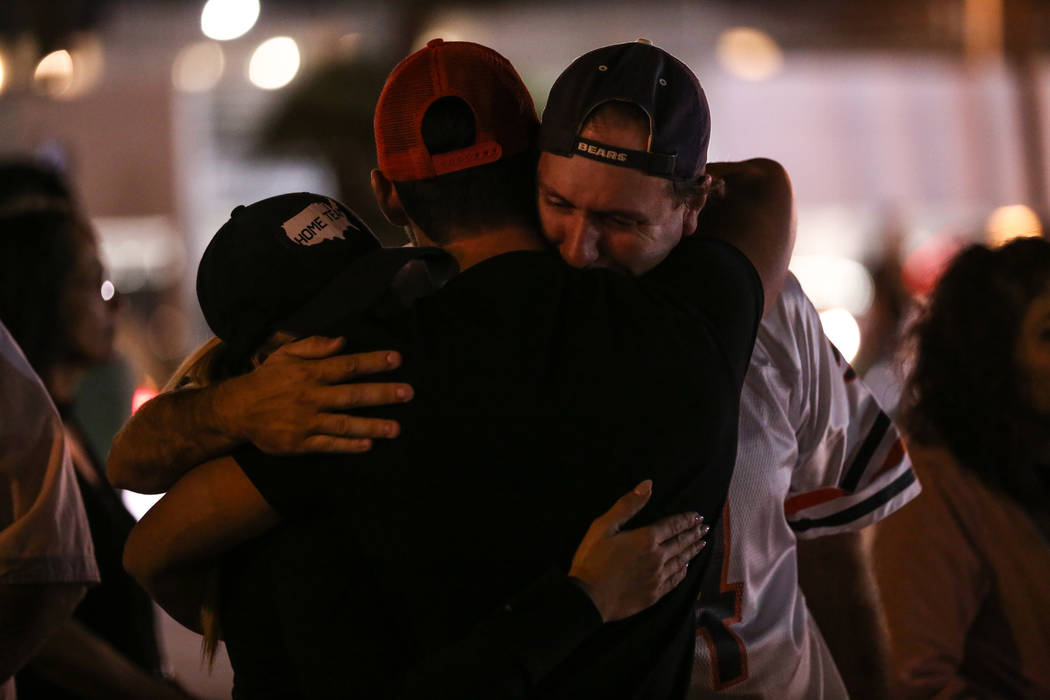 Kristy-Marie Hoff, 32, center, Andrew Fusaro, 23, center, and Sean Kelly, 42, right hug as some lights along the Strip turned off at 10:05 p.m. for 11 minutes marking exactly one week after the ma ...