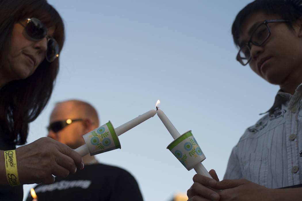 Lisa Czarny, left, lights James Ceredon's candle during a vigil on the corner of Sahara Avenue and Las Vegas Boulevard in Las Vegas, Sunday, Oct. 8, 2017.  Bridget Bennett Las Vegas Review-Journal ...