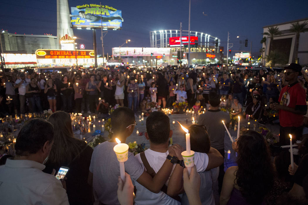 Attendees raise candles during a vigil in honor of the victims exactly one week after the mass shooting on Oct. 1, 2017, on the corner of Sahara Avenue and Las Vegas Boulevard in Las Vegas, Sunday ...