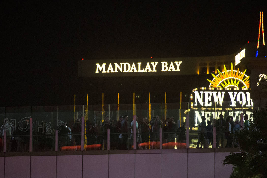 Pedestrians stand on top of a walking bridge as marquees on the Strip go dark one week after the Oct. 1, 2017 mass shooting in Las Vegas, Sunday, Oct. 8, 2017. Bridget Bennett Las Vegas Review-Jou ...