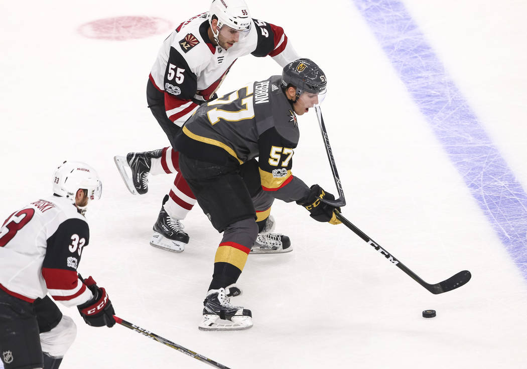 Vegas Golden Knights left wing David Perron (57) controls the puck as he is pressured by Arizona Coyotes defenseman Jason Demers (55) and Coyotes defenseman Alex Goligoski (33) during the first pe ...