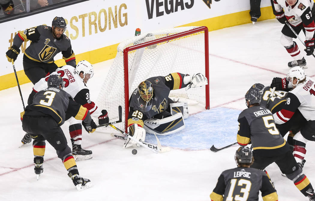Vegas Golden Knights goalie Marc-Andre Fleury (29) deflects a shot from Arizona Coyotes right wing Christian Fischer (36) during the third period of an NHL hockey game between the Vegas Golden Kni ...