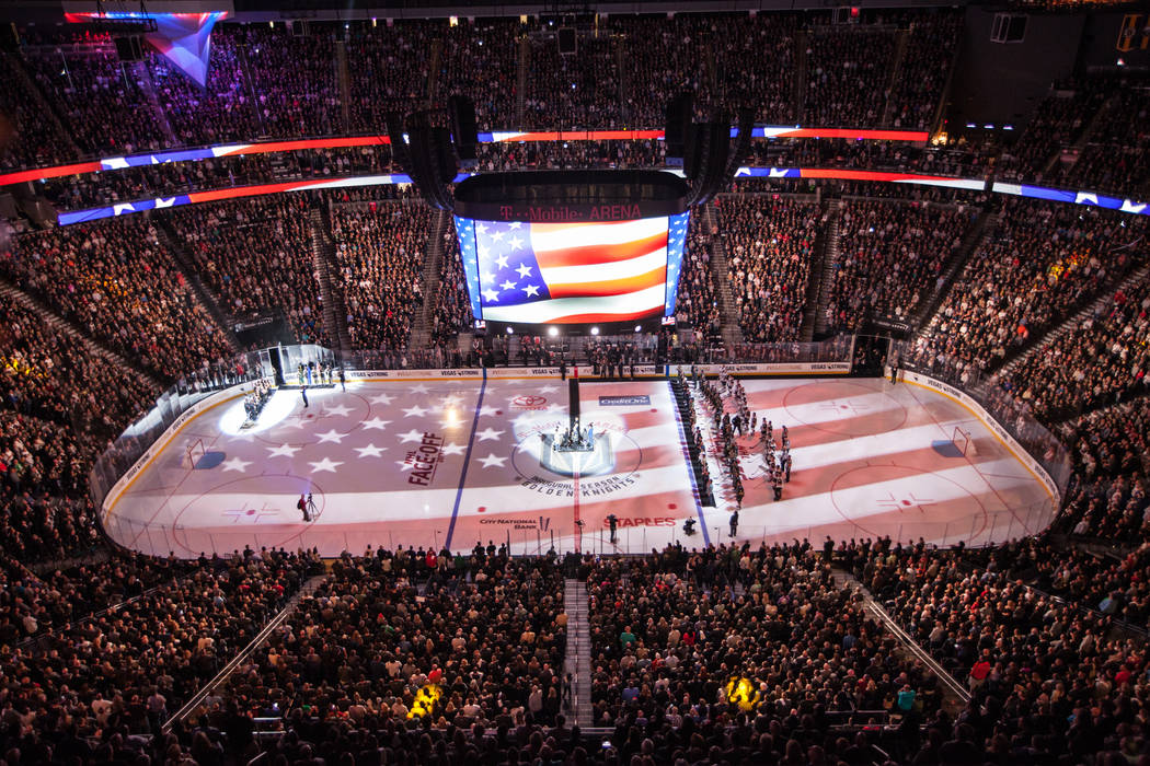 The American flag is displayed on the hockey ring during a ceremony honoring victims and first responders of the Route 91 Harvest Festival shooting before the start of an NHL hockey game between t ...