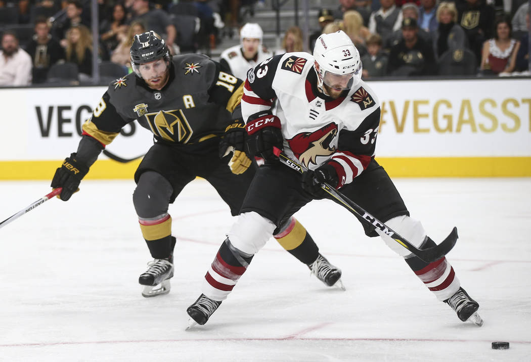 Arizona Coyotes' Alex Goligoski (33) controls the puck as Vegas Golden Knights' James Neal (18) follows after during an NHL hockey game at T-Mobile Arena in Las Vegas on Tuesday, Oct. 10, 2017. Th ...