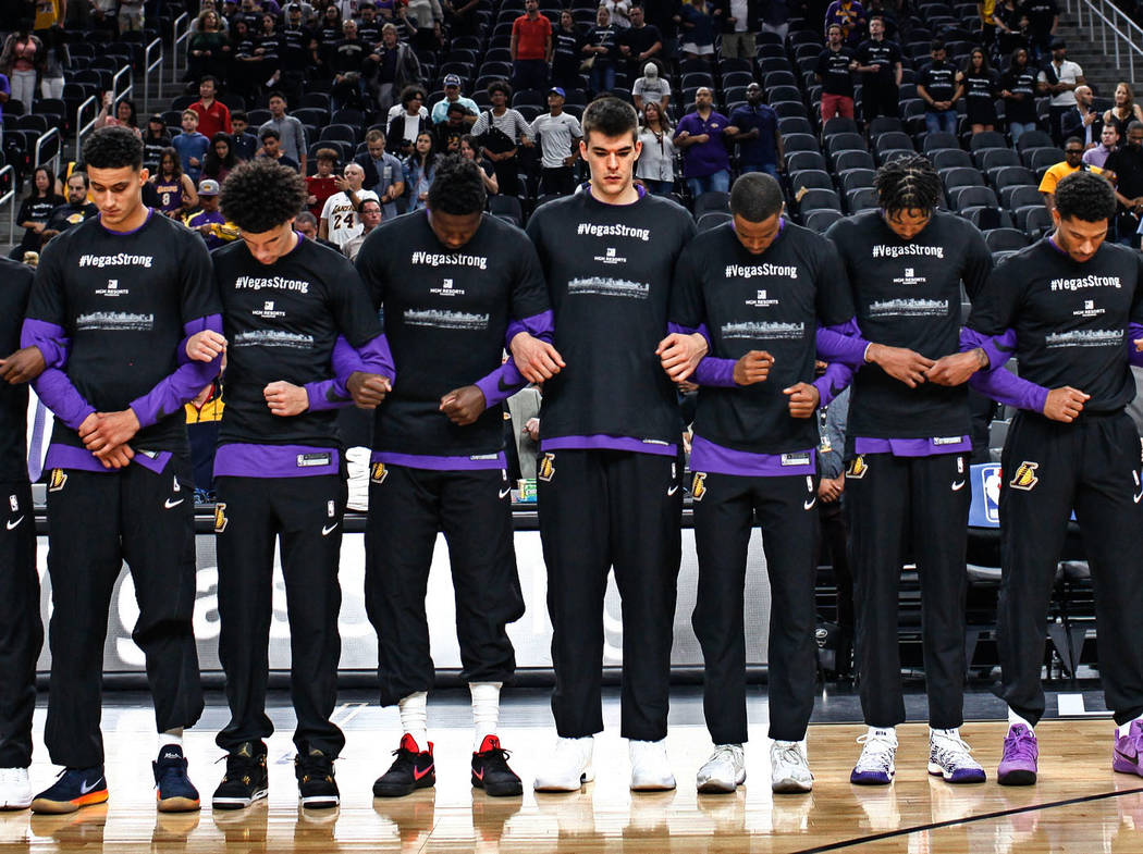 The Los Angeles Lakers link arms during a moment of silence for the victims of last week's mass shooting during the opening of a preseason basketball game against the Sacramento Kings at T-Mobile  ...