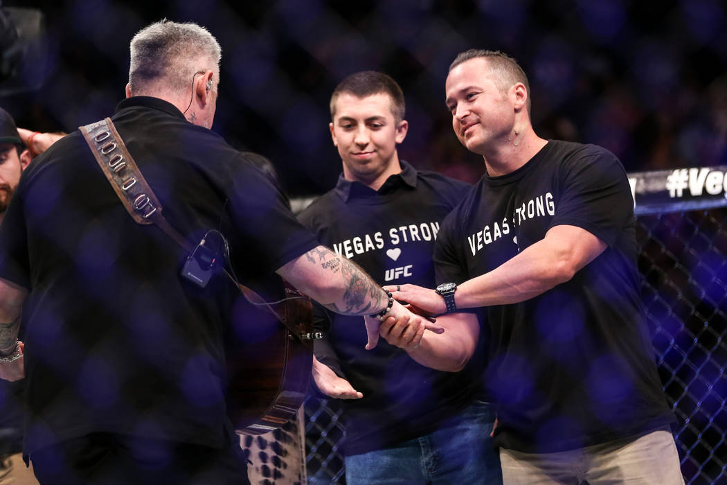 Las Vegas police officer Brady Cook, center, and injured Detective Casey Clarkson, right, shake hands with Everlast as they are honored along with other victims of Sunday night's mass shooting dur ...