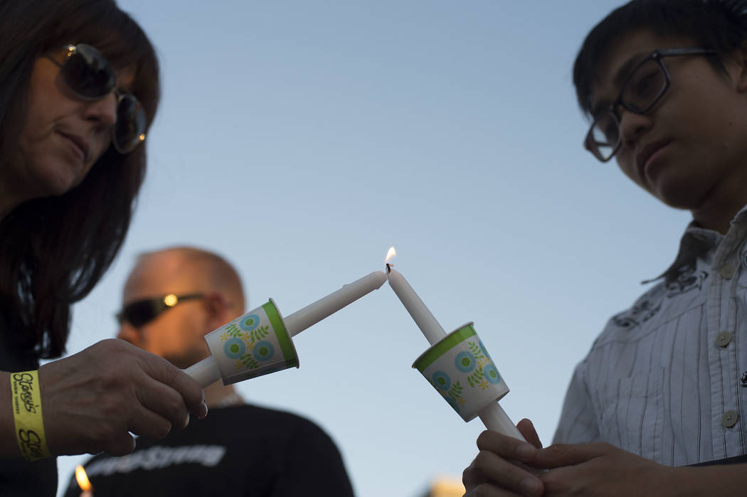 Lisa Czarny, left, lights James Ceredon's candle during a vigil on the corner of Sahara Avenue and Las Vegas Boulevard in Las Vegas, Sunday, Oct. 8, 2017.  Bridget Bennett Las Vegas Review-Journal ...