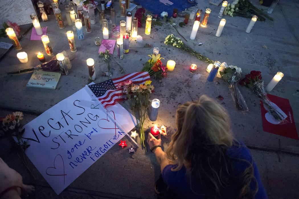 Chelsey Kade lights a candle during a vigil on the corner of Sahara Avenue and Las Vegas Boulevard in Las Vegas, Sunday, Oct. 8, 2017.  Bridget Bennett Las Vegas Review-Journal @Bridgetkbennett