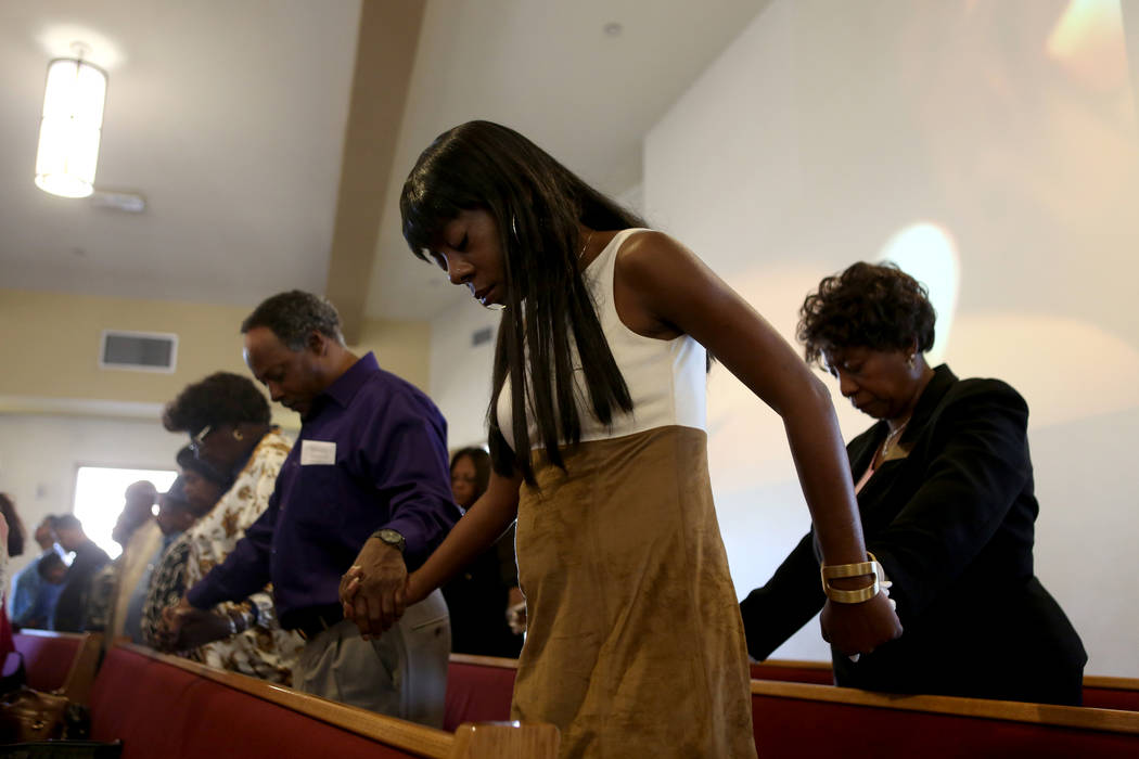 Yvette Sallie links hands with other church attendees while the fallen Route 91 Harvest festival victims' names are read during a First African-Methodist Episcopal Church service in North Las Vega ...