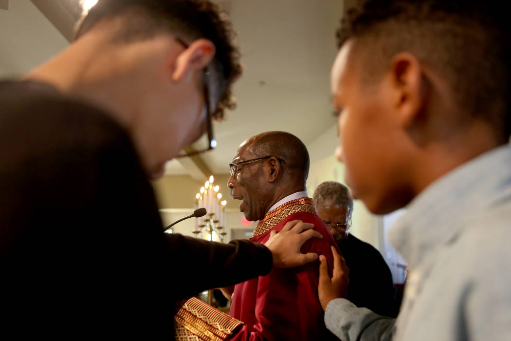 Jassir Vega, 14, left, and Kole Candley, 11, right, lay their hands on Senior minister Rev. Ralph E. Williamson during a prayer at the First African-Methodist Episcopal Church in North Las Vegas,  ...