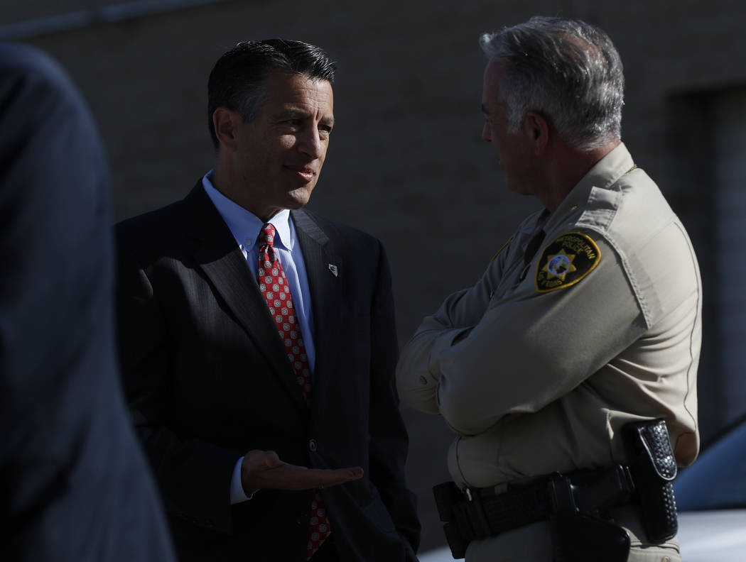 Gov. Brian Sandoval, left, and Clark County Sheriff Joe Lombardo talk while waiting for the arrival of President Donald Trump at McCarran International Airport in Las Vegas on Wednesday, Oct. 4, 2 ...