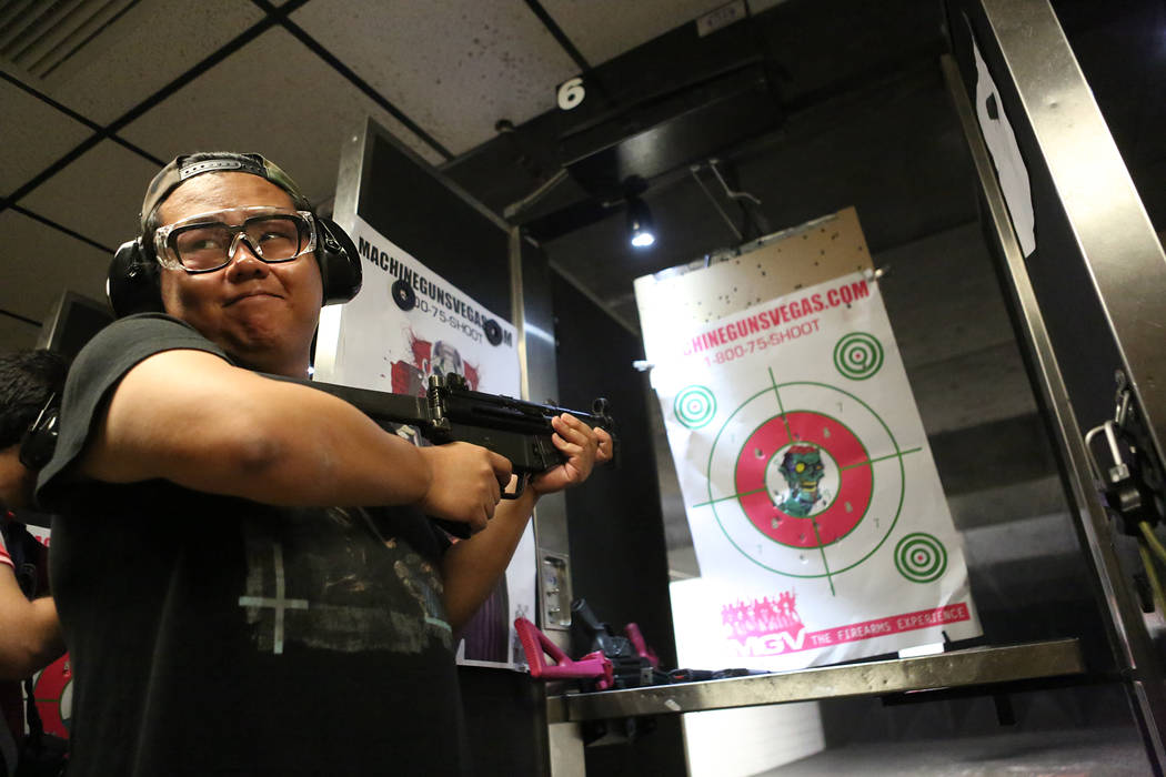 Xiao Chen of Beijing looks back to companion Chrissy Shen after firing an MP5 submachine gun at Machine Guns Vegas on Wednesday, Aug. 30, 2017. (Michael Quine/Las Vegas Review-Journal) @Vegas88s