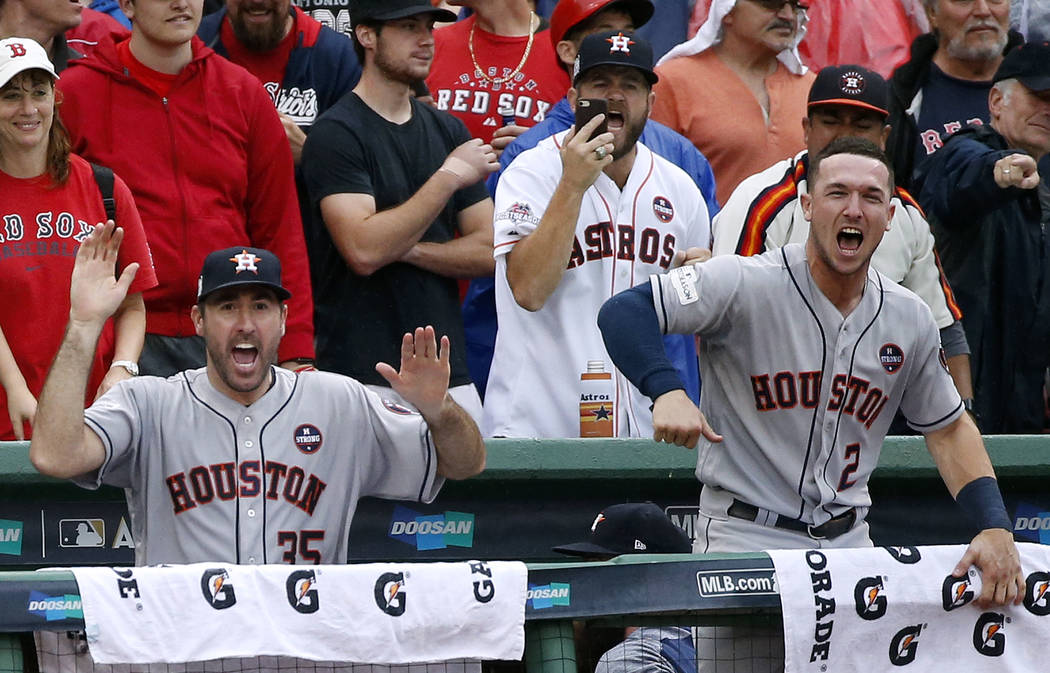Houston Astros relief pitcher Justin Verlander, left, and Houston Astros third baseman Alex Bregman, right, cheer after Josh Reddick hit an RBI single in the eighth inning in Game 4 of baseball's  ...