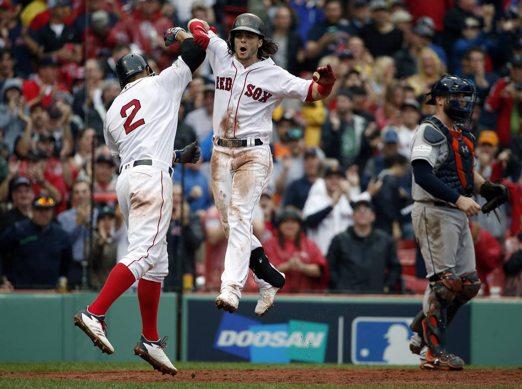 Boston Red Sox's Andrew Benintendi, center, celebrates his two-run home run with Xander Bogaerts, left, during the fifth inning in Game 4 of baseball's American League Division Series against the  ...