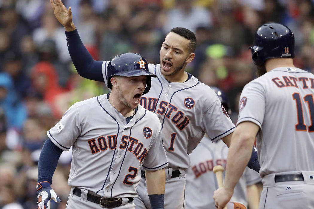 Houston Astros third baseman Alex Bregman (2) celebrates his home run with Carlos Correa, rear, and Evan Gattis, right during the eighth inning of Game 4 in baseball's American League Division Ser ...