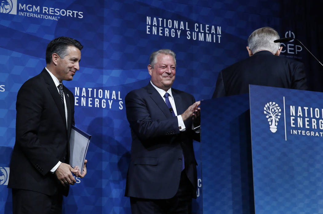 Former U.S. Senate Harry Reid, right, (D-Nev.) leaves the podium as Gov. Brian Sandoval, left, and former Vice President Al Gore look on during the National Clean Energy Summit Friday, Oct. 13, 20 ...