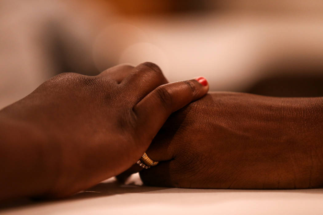 Minna Abdul Rahman, 12, left, and Amel Ageeb, 43, right, both living in Las Vegas, hold hands during a prayer service at the Masjid Ibrahim mosque in Las Vegas, Monday, Oct. 9, 2017. The service w ...