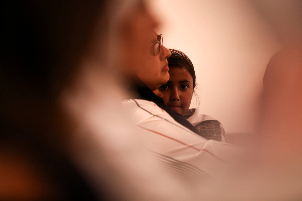Rabiya Suba of Las Vegas, 6, right, sits on her mother, Aliyah's lap, 35, left, during a prayer service at the Masjid Ibrahim mosque in Las Vegas, Monday, Oct. 9, 2017. The service was held in rem ...