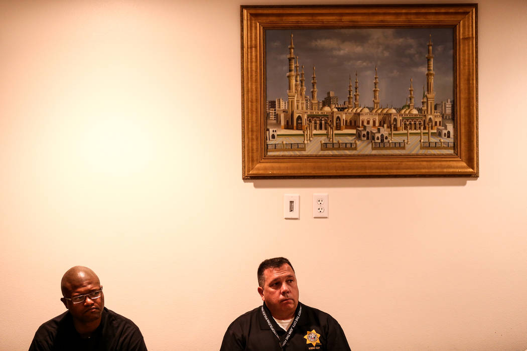 Hakeem Later of Las Vegas, 26, left, and Las Vegas Metro Police Officer Vince D'Angelo, right, sit during a prayer service at the Masjid Ibrahim mosque in Las Vegas, Monday, Oct. 9, 2017. The serv ...